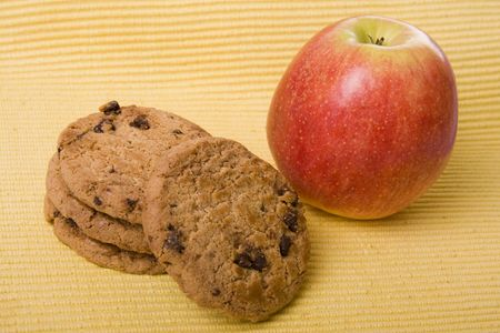 Chocolate cookies and a red apple on a yellow background photo