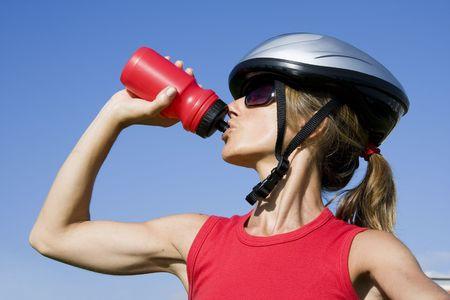 Sportliche Frauen mit einem Fahrradhelm Trinkwasser
