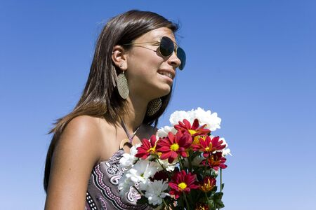 Young girl holding a bouquet of red and white flowers on a blue sky Stock Photo - 5639798