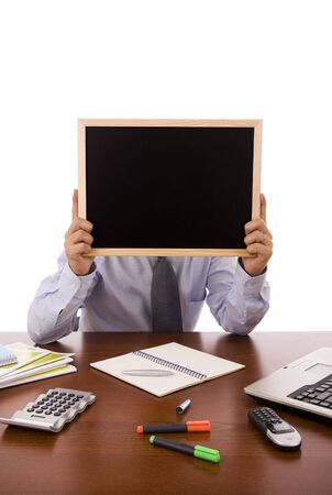 Buiness man sit at his desk holding a blank blackboard  photo