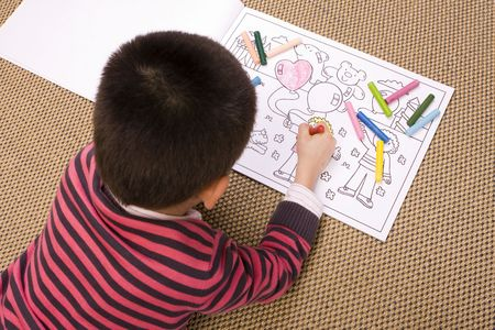 Young boy lying on the floor painting a drawing Stock Photo - 6446579