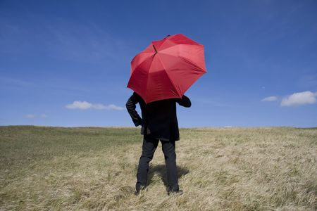 Business man with an umbrella on the meadow photo