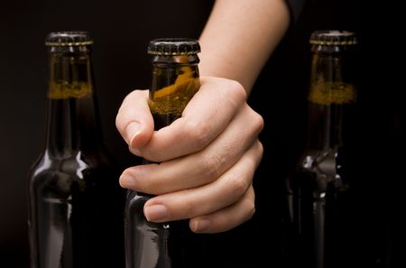 Close-up of a female hand holding a bottle beer isolated on black photo
