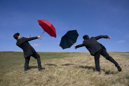 Business concept with two men holding umbrellas for protection  photo