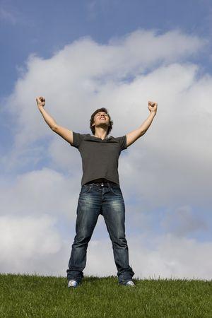 manos levantadas al cielo: Joven con sus brazos extendidos  Foto de archivo