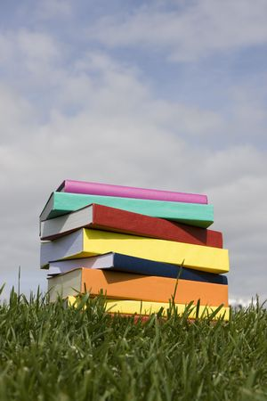 A stack of colorful books on the grass photo