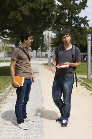 Two college or university students walking on a park path photo