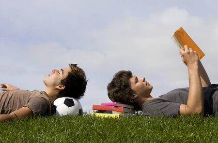 Two young students lying on the grass  photo