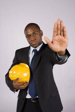 Young engineer holding a yellow helmet ordering to stop with his hand photo