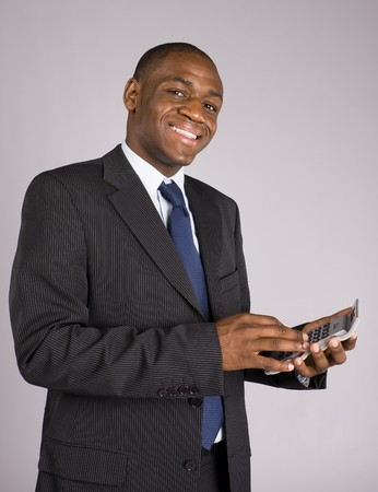 Happy young business man doing some calculations photo
