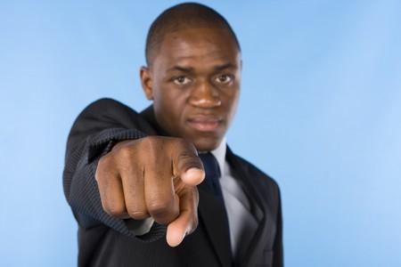 dedo indice: Hombre de negocios graves apuntando a usted (enfoque en su dedo)  Foto de archivo