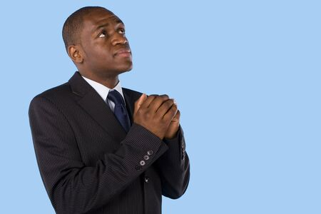 religious clothing: A business man praying and looking up to god Stock Photo