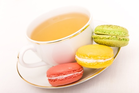 Cup of tea with three colorful macarons photo