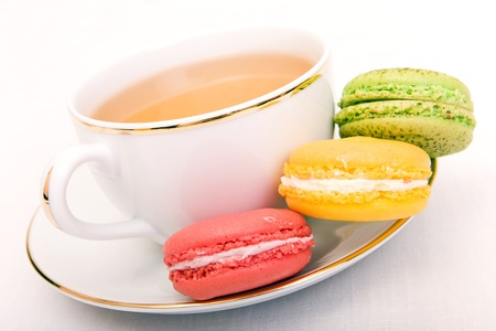 Cup of tea with colorful french macaron photo