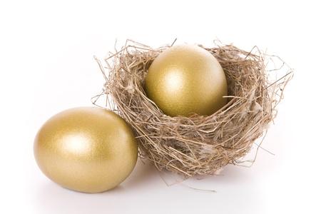 huevos de oro: Guardar el concepto - dos huevos de oro y un nido aislados en blanco
