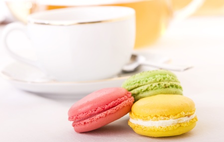 Colorful macaron with a cup of tea - Focus on the yellow one photo