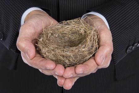litle: Business man holding a litle empty nest