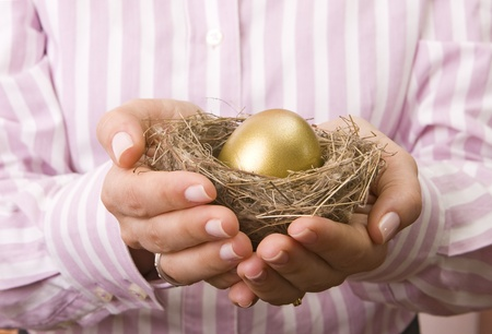 Woman�s hand holding a nest with a golden egg inside photo