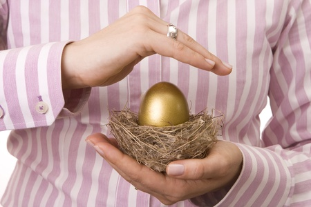 bank protection: Woman´s hand protecting a nest with a golden egg inside Stock Photo