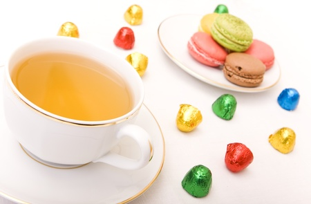 Cup of tea with some colorful chocolates and macaron photo