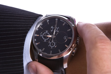 looking at watch: Businessman checking the time on his watch Stock Photo