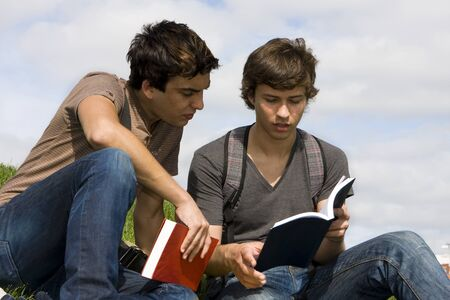 Two young students sit on the grass reading a book Stock Photo - 10108859