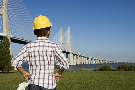 inspect: Little boy with gloves and a helmet looking to a bridge