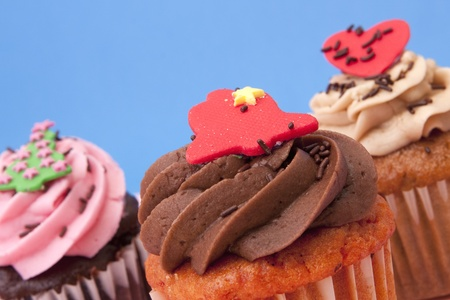 Close up of three cupcakes on a blue background Stock Photo - 12679844