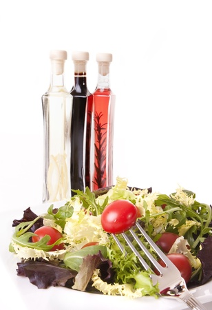 Healthy food concept - Tomatoes and green salad with styled aromatic vinegar bottle on background photo