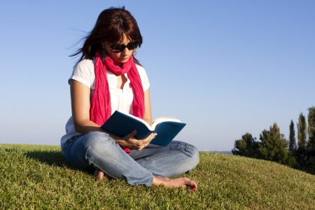 Beautiful woman reading a book on the park photo