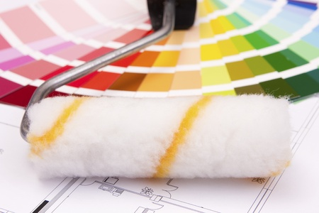 ordinate: Color samples for selection and a a painter�s roll with house plan on background Stock Photo