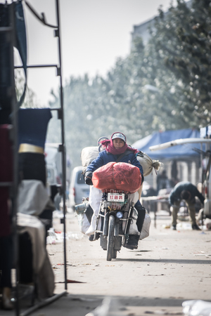 wage earners: women seller going home with bike Editorial