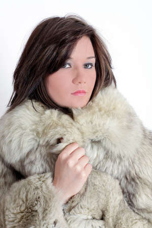 Portrait of a young brunette russian teenager girl with fur in studio Stock Photo