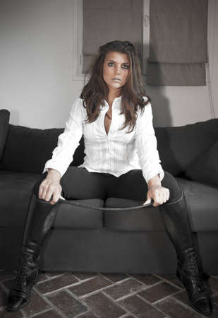 Provocative girl on sofa with horsewhip
