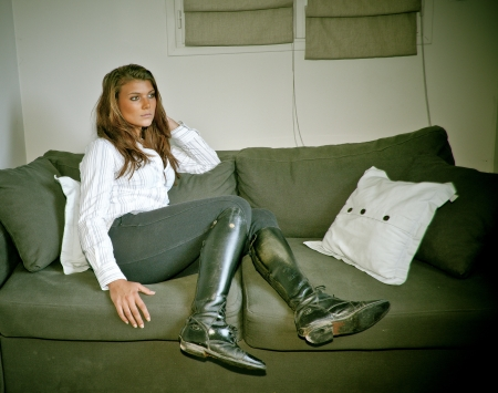 young sensual horsewoman lying on a sofa with hand in her hair