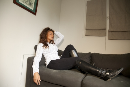 young sensual horsewoman lying on a sofa with hand in her hair photo
