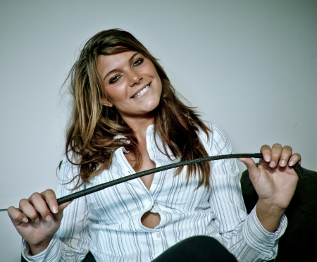 smiling provocative young woman with an horsewhip in her hand