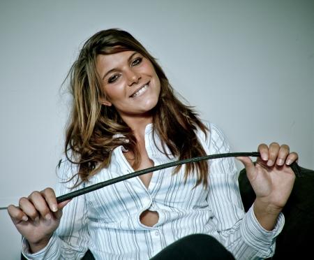 lächelnd provokativ junge Frau mit einer Peitsche in der Hand