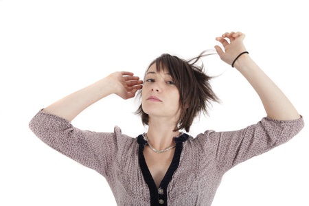 portrait of a young brunette playing with her hair on studio looking ahead