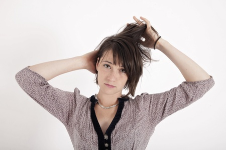 portrait of a young woman in grey dress playing with her hair on studio Stock Photo