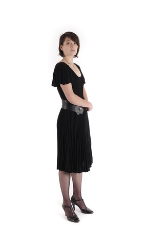 a young woman in strict black dress in studio looking like widow or nanny