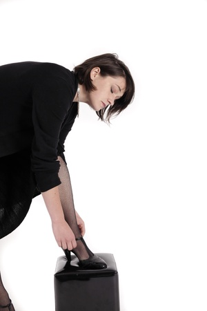 young brunette woman looking like a nanny or widow wearing a black shoe photo