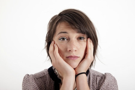 young woman looking ahead with hand under her face isolated in studio