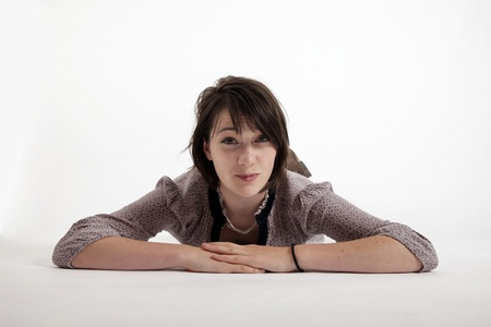 young brunette woman lenthened on the ground isolated in studio looking ahead