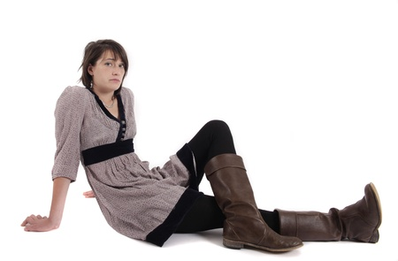 young brunette woman in dress sitting on the ground with boots