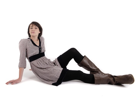 young brunette woman in dress sitting on the ground with boots photo