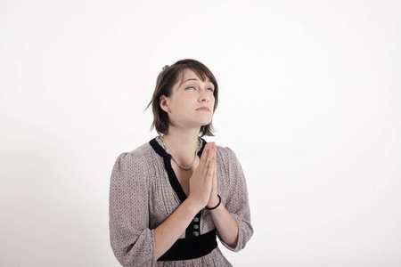 requesting: portrait of a young brunette woman requesting in catholic posture united hand Stock Photo