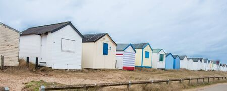 A row of beach huts on a dull winters day by the seaside. Stock Photo