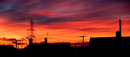 power cables: A vivid red sunset over the towns roofs showing all the power and telephone cables Stock Photo