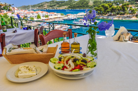 skiathos: Old Skiathos restaurant, over looking the harbour with boats in a blue sea and a Greek salad waiting to eaten. Stock Photo